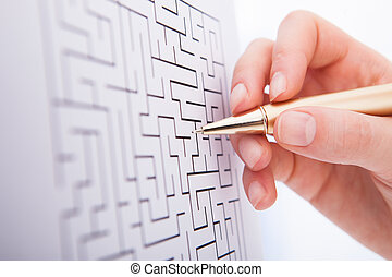 Businesswoman Solving Maze Puzzle - Cropped image of...