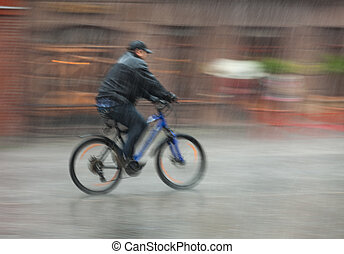 cyclist rides through the streets on a rainy day - Downpour....