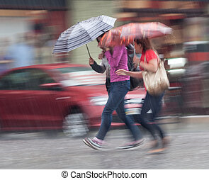 People walking down the street in rainy day - Group of young...