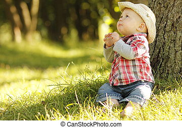 little boy playing cowboy in nature - a little boy playing...