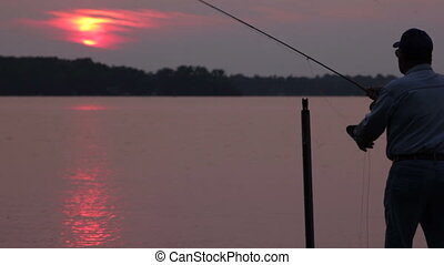Fishing at sunset - Senior man, fly-fishing (casting) off...