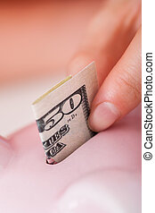 Hand Inserting 50 Dollar Bill In Piggybank - Closeup of...