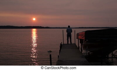 Fishing at sunset - Senior man, fly-fishing casting off the...