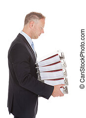 Sad Businessman Carrying Stack Of Binders - Side view of sad...
