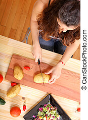 Cooking Vegetarian - A young woman cutting vegetables ion...