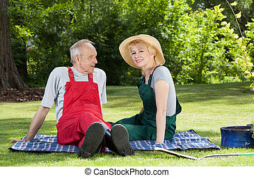 Couple sitting on a blanket in the garden - Senior couple...