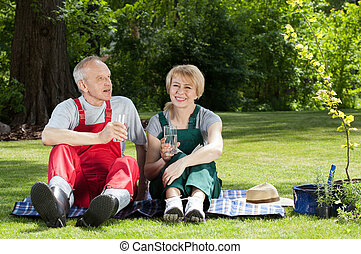 Couple sitting on a blanket and drinking water - Gardener...
