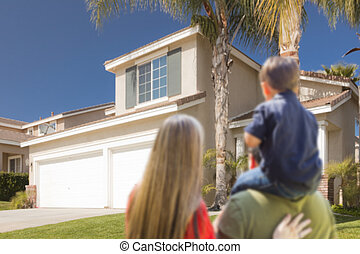 Mixed Race Young Family Looking At Beautiful Home