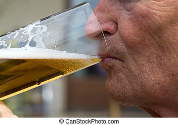 Mature man drinks beer. Best is the first draught