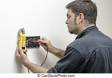 Technician working on a thermostat - HVAC technician testing...