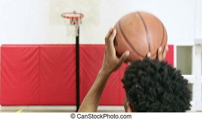Basketball - Man shooting basketball in a gymnasium