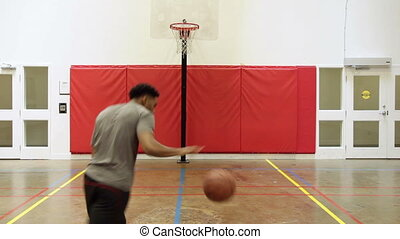 Basketball - Man shooting basketball in a gymnasium
