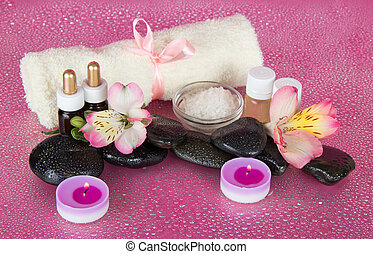 Spa set, candles and towel on pink background