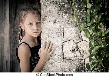 Portrait of sad little girl standing near stone wall in the...