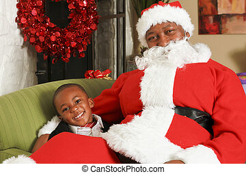 Santa sitting on little boy's lap - Little boy smiling...
