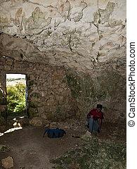 Archeologist examining floor of a troglodyte dwelling cave...