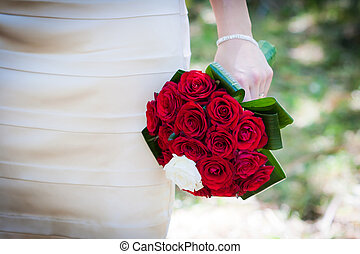 Bride holding a wedding bouquet with red roses