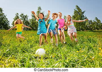 Playful friends running to the ball in field - Playful...