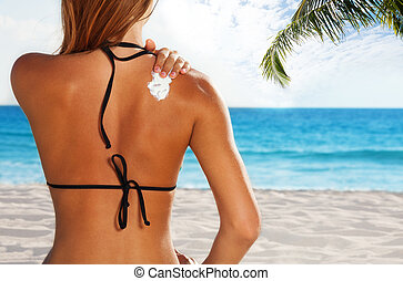 Woman applying sun protection on tanned back - Woman...