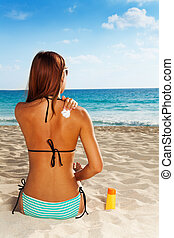 Applying sun protection on tanned skin - Back of gorgeous...