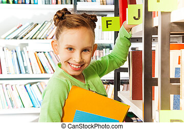 Smiling girl searching books in library