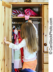 Cute little girl hanging up her clothes into the wardrobe