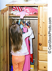 Cute little girl hanging up her clothes