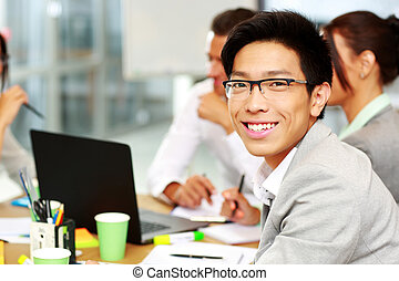 Portrait of a smiling businessman sitting in front of...
