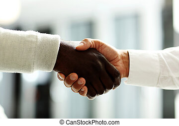 Close-up of businessmen shaking hands, Caucasian and...
