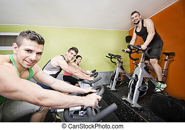 Spining class - Four guys at gym in indoor spnining class
