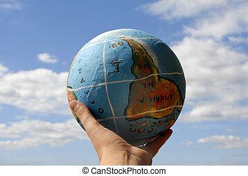 globe in a woman\'s hand and the sky