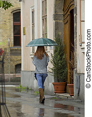 Rainy day - Pretty girl with umbrella walking down the...