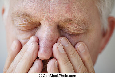 Sinus problems in senior man - closeup of man with fingers...