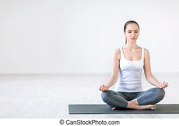 Meditation - Young woman doing yoga in a studio
