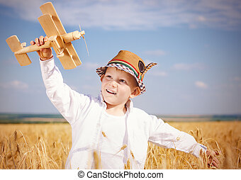 Trendy young boy playing in a field with a plane - Trendy...