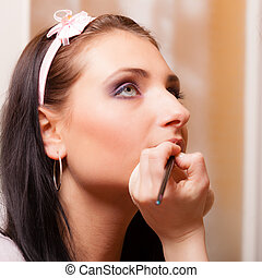 Makeup artist applying with brush lipstick on lips of woman...
