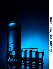 Bottle of vodka with many glasses lit with blue backlight -...