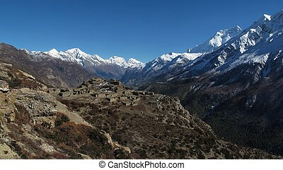 Ruins of a old village near Manang and high mountains of the...