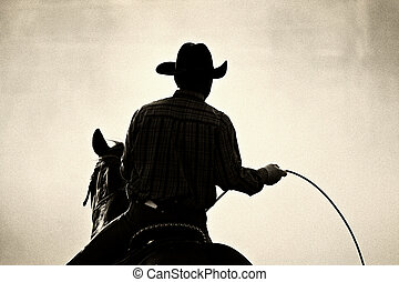 cowboy rodeo - cowboy at the rodeo - shot backlit against...