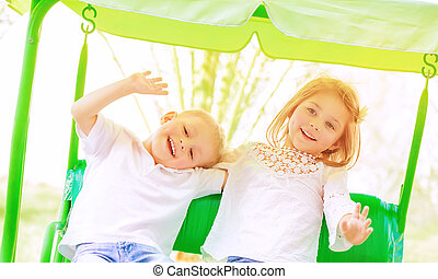 Happy kids on the swing - Cute little brother and sister...