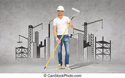 handsome painter in helmet with paint roller - construction...