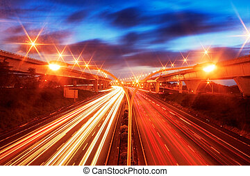 Night skyline view of city and highways with flowing...
