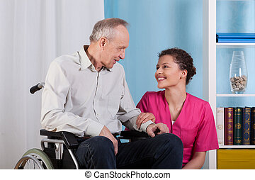 Nurse smiles to sitting in a wheelchair patient