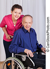 Smiling nurse standing by the disabled