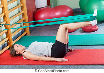 Girl lying on exercise mat and stretching legs with elastic...