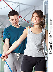 Personal trainer helping girl during exercises - Personal...