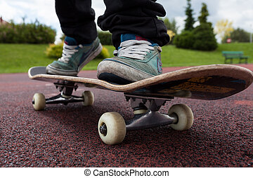 Young person rides on skateboard on court