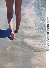 Female legs closeup walking on the sandy beach