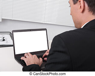Rear view of businessman busy using laptop at office desk