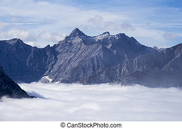 high mountain in austria with rock wall and clouds
